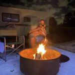 Man and dog hanging out around fire pit