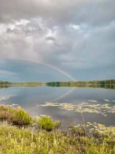 rainbow over lake with lily pads after storm