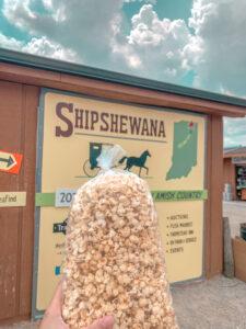 Bag of kettle corn popcorn in front of Shipshewana sign