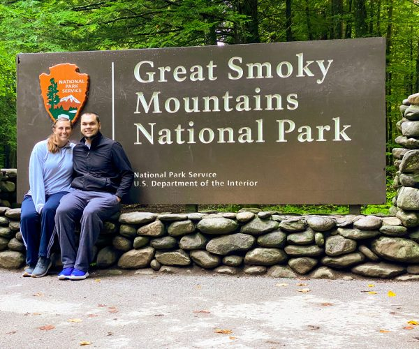 Couple sitting in front of Great Smoky Mountains National Park sign