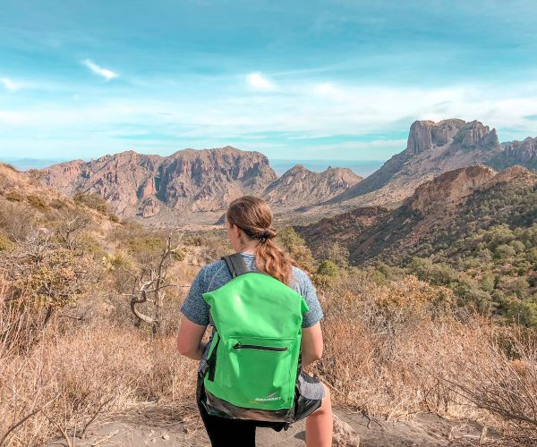 Megan wearing green backpack overlooking mountains during hike