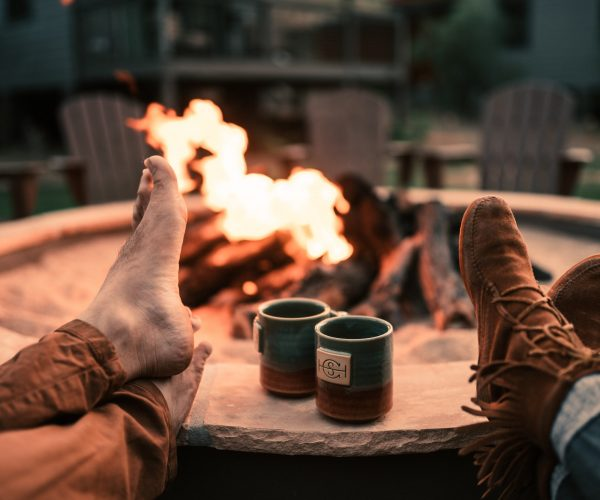 feet propped up by fire