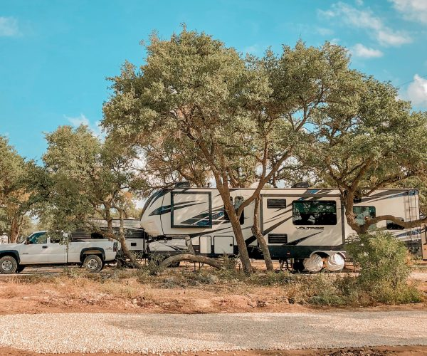 White fifth wheel at campsite under trees